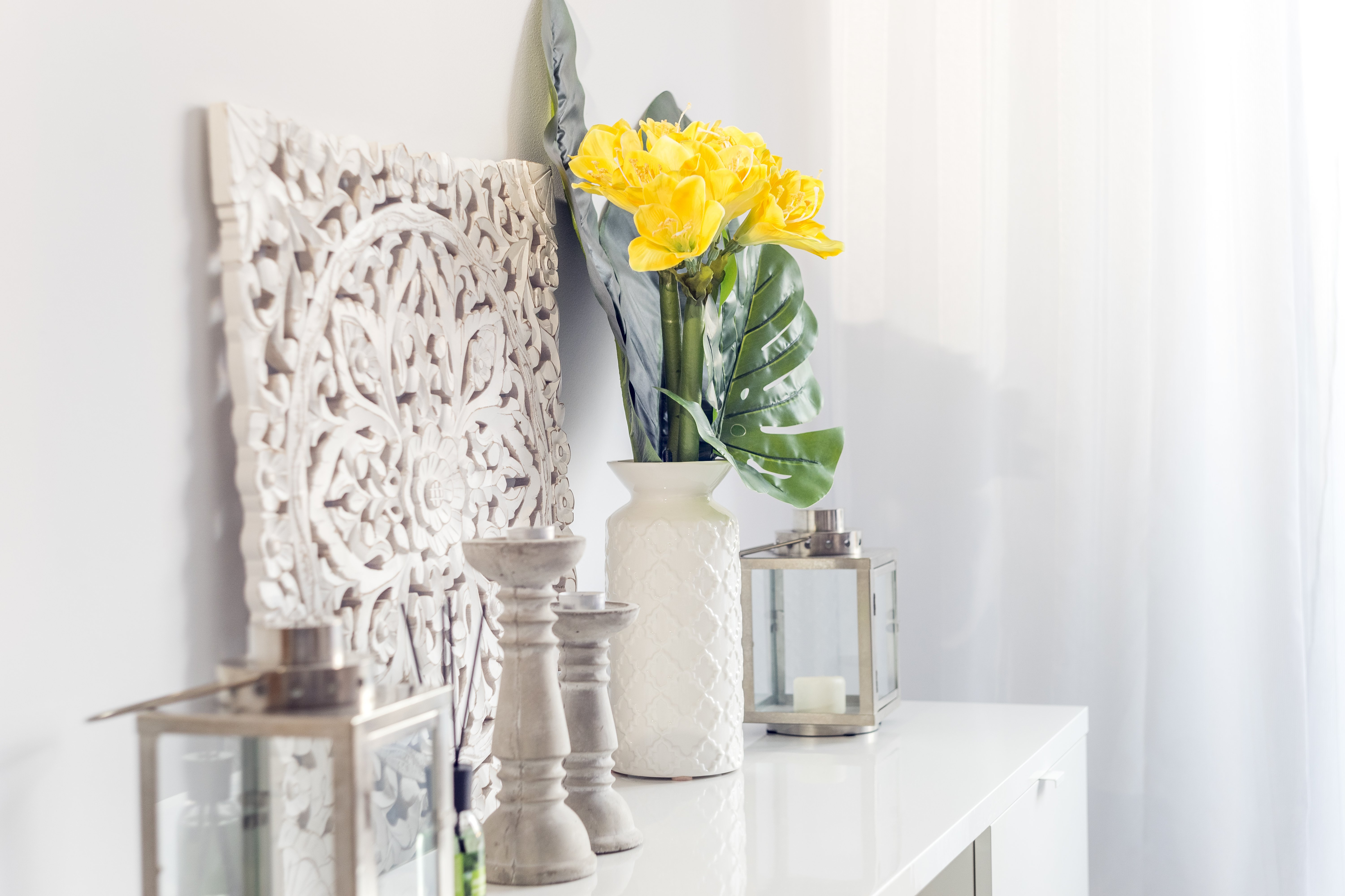 Yellow flowers in ceramic vase with wooden candlesticks and lantern decorating a shelf in a living room